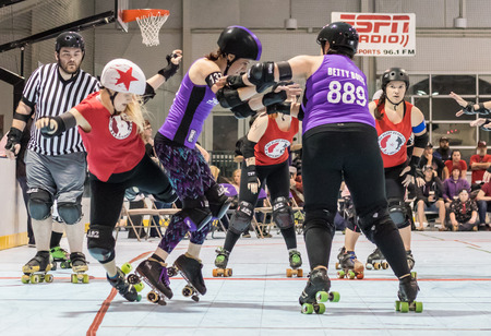Roller derby action with Red Bluff Derby Girls (red) and Shasta Roller Derby girls in Redding, California. Editorial
