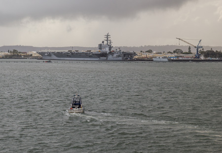 aircraft carrier: San Diego, California, USA-December 21, 2010: A Shelter Island Police boat is on patrol in San Diego Harbor with the USS Ronald Reagan aircraft carrier in the background.