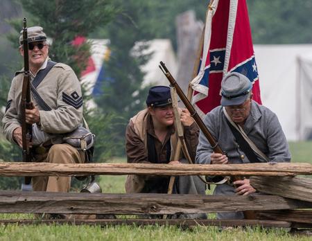 vestidos de epoca: Soldados de la guerra civil en la acción en la recreación Dog Island en Red Bluff, California. Editorial