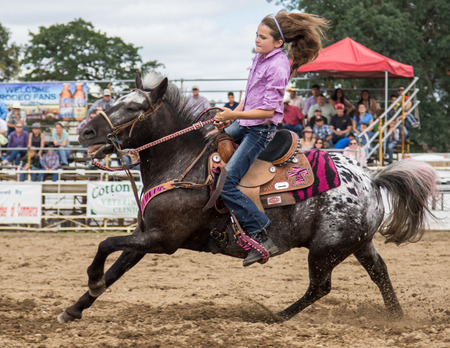 arena rodeo: Barrel racing action at the Cottonwood Rodeo in northern California on May 8th, 2016. Editorial