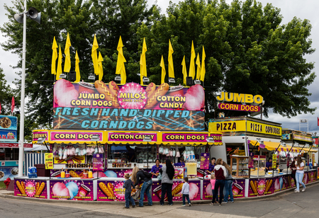 Concession stand, ticket booth, rides, and games at the county fair . Editorial