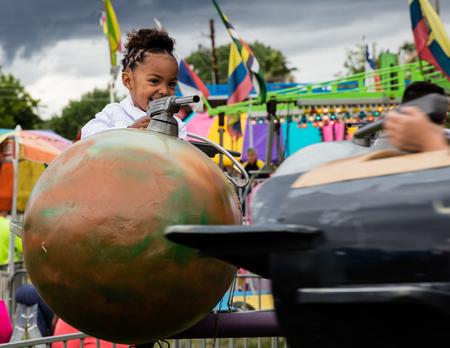 niños actuando: Los niños disfrutan de un paseo en la Feria del Condado de Shasta en Anderson, California.