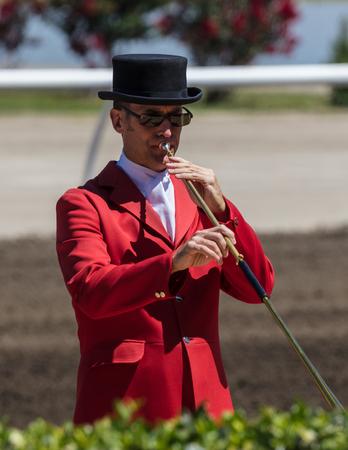 Bugler en chapeau haut-de-forme et manteau joue Cal à la poste aux courses de chevaux à Sacramento, en Californie. Banque d'images - 82712261