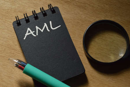 Tip view of pen, magnifying glass and notebook written with AML stands for Anti Money Laundering