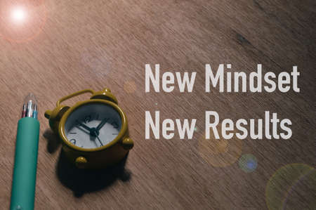Top angle view of clock over wooden background written with text NEW MINDSET NEW RESULTS.