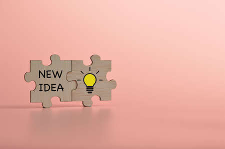 Light bulb on jigsaw puzzle with text NEW IDEA. Copy space