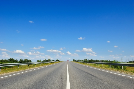 roadway: Countryside road leading straight to cloudy blue sky