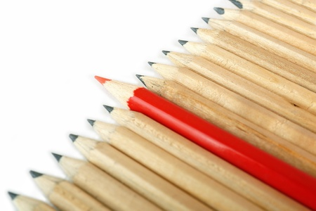 distinction: Row of rough graphite pencils with color red one as a symbol of difference and opposition