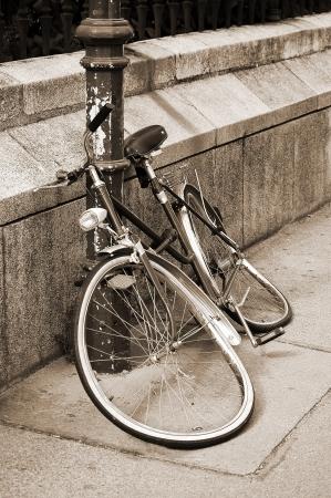 보도 세피아 톤의 이미지에 철 기둥에 고정 버려진 손상 자전거 스톡 콘텐츠
