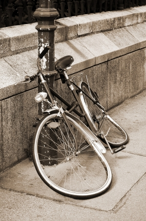 parked bicycles: Abandoned damaged bicycle locked to an iron pillar on sidewalk  Sepia toned image