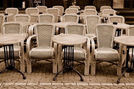 Empty dining tables and rattan wicker chairs in a street cafe, Amsterdam photo