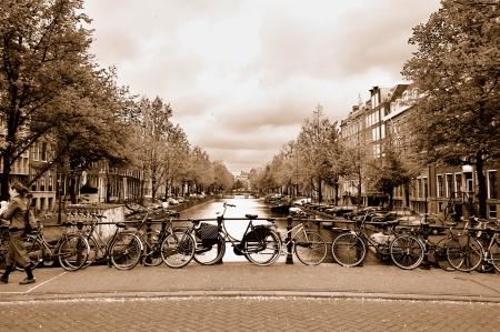 흐린 봄 날에 세피아 톤의 이미지에서 운하를 가로 지르는 다리에 자전거와 함께 암스테르담 센터의 전형적인보기