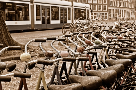 A lot of colored bicycles at the bike rental station on a rainy day in Amsterdam  Sepia toned image  photo