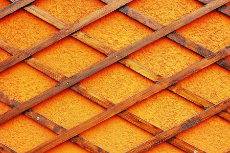 trellis: Wooden trellis with rhomb shaped holes fastened to plastered orange wall