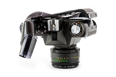 Close-up view of a opened classic manual SLR film camera with film on white background photo