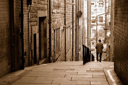Man in hat walking down an alleyway in the Old Town of Edinburgh photo