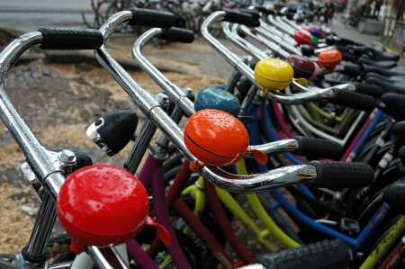A lot of colored bicycles at the bike rental station on a rainy day in Amsterdam
