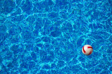 Beach ball floating in the blue clear water of swimming pool with mosaic bottom photo