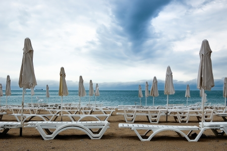 morose: Dead season  Rows of closed umbrellas and deckchairs on the empty beach before a storm  Stock Photo