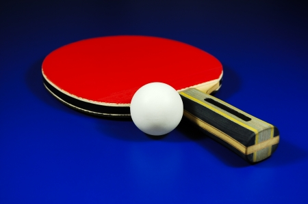 Table tennis racket and ball on blue table
