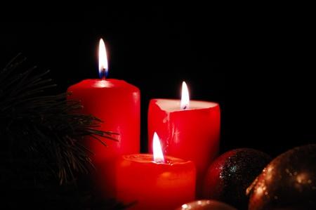 Three burning candles with seasonal decorations. Low key lighting.