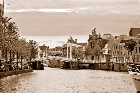 Beautiful view at Gravestenenbrug, the famous draw bridge over the Spaarne river in Haarlem in overcast spring day. Sepia toned image.