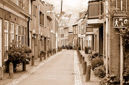 View of a small cosy side street in Haarlem in overcast spring day. Sepia toned image. photo