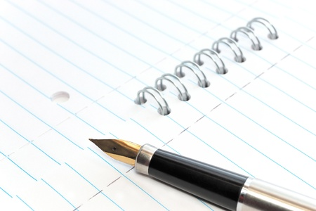 writing lines: A gold-nibbed pen on a spiral-bound notepad