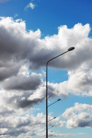 dramatically: A row of street lamps against the dramatically overcast sky
