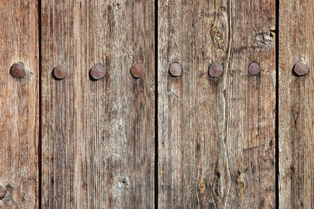 Weathered wooden fence texture with rusty forged nail heads photo
