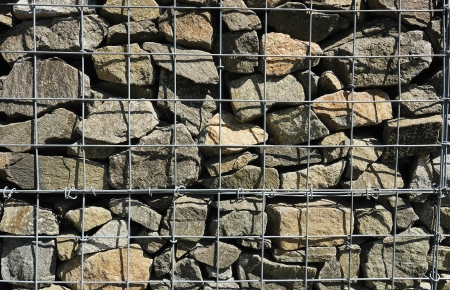 A fragment of wall made of wired cage filled with stones (gabions) photo