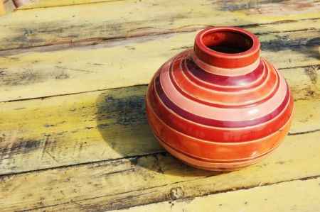 A colored stripped vase on the weathered yellow wooden table