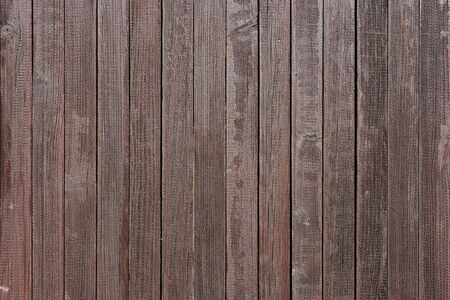 Dark brown painted weathered wooden fence texture