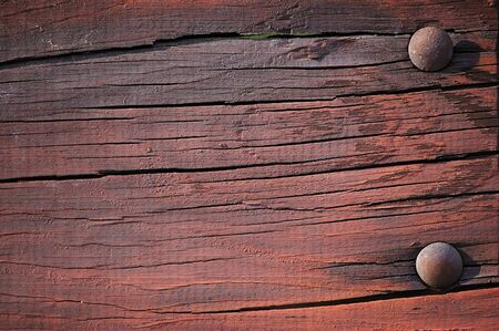Weathered dark painted plank with bolt head close-up photo