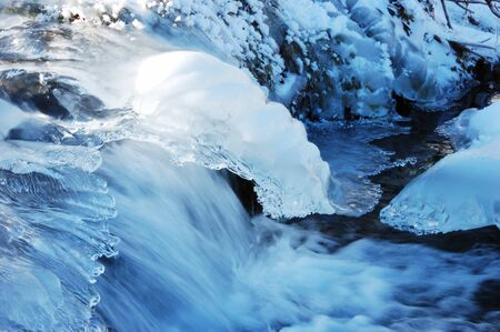 A mountain river with small iced cascade  Stock Photo