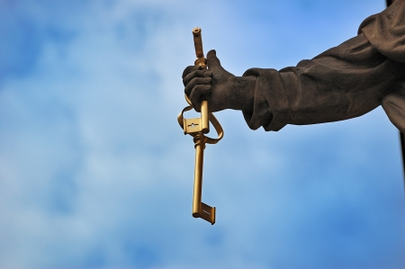 saint peter: Fragment of Statue of Saint Peter the Apostle: hand holding keys of the kingdom of Heaven against cloudy blue sky Stock Photo