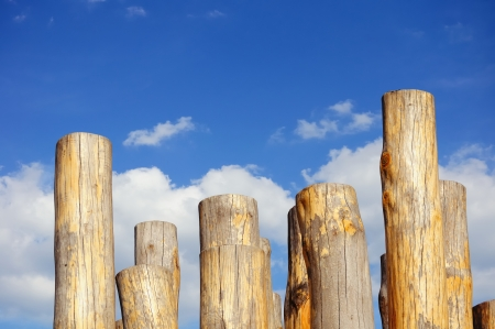 stockade: Wooden columns against cloudy blue sky Stock Photo