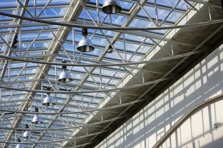 유리와 푸른 하늘 배경에 램프의 행과 함께 만든 지붕으로 현대적인 건물의 조각