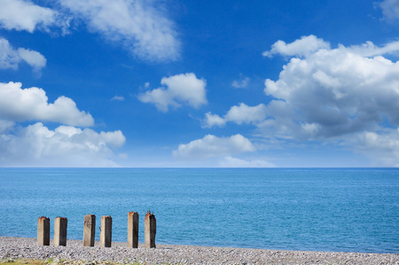 Concrete columns of an old decayed pier on the pebbly beach against the picturesque cloudy sky Stock Photo