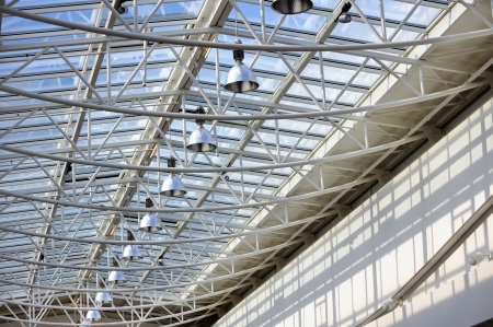 roof beam: Fragment of modern building with roof made of glass and metal with row of lamps against blue sky background