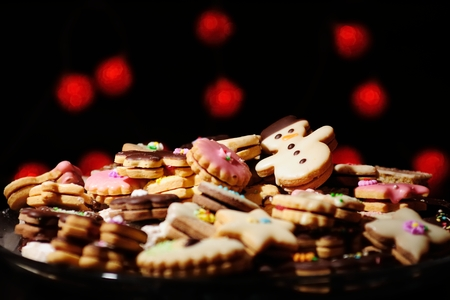 Lots of Christmas cookies and cakes against the background of blurred warm red lights photo