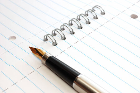 ruled paper: A gold pen on a spiral-bound notepad