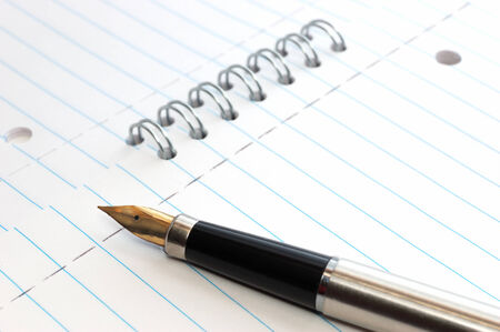 ruled paper: A gold-nibbed pen on a spiral-bound notepad