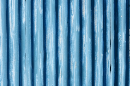 goffer: Corrugated metal sheet fence with peeling away paint