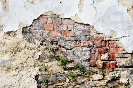 Fragment of tumbledown plastered brick wall