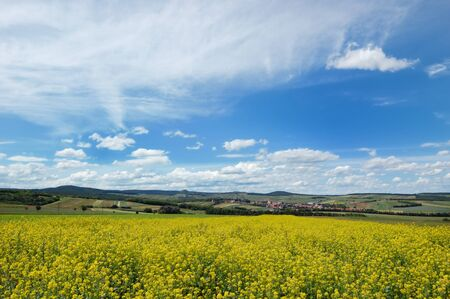 Picturesque view of hilly countryside area with rapeseed filed in the foreground