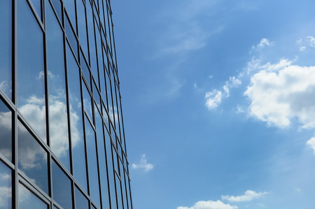 sky reflection: Reflection of cloudy sky in glass wall of modern office building