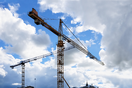 Construction tower cranes against a partly cloudy bright blue sky