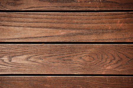 Weathered brown painted wooden plank close-up