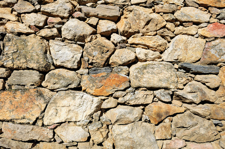 Fragment of wall made of rough uneven mixed stones